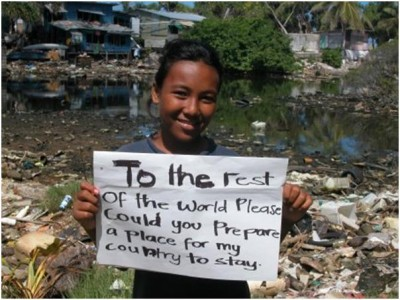 A young woman from Tuvalu holds up a sign asking for a place to live as her own home suffers from sea level rise in the background. Image source